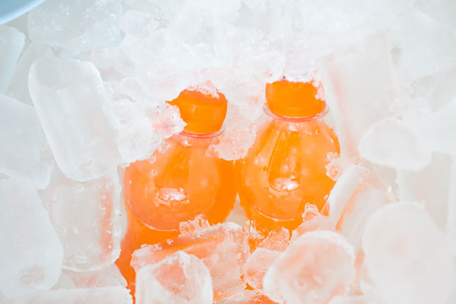 Fresh orange juice in plastic bottle on ice