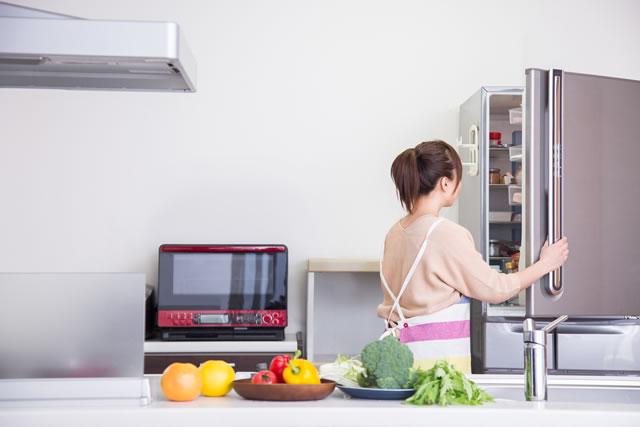冷蔵庫を開けて野菜を出している女性