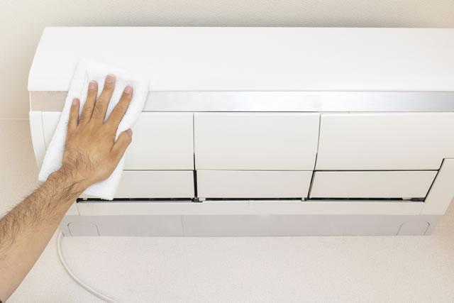 タオルでエアコンの外観を拭き掃除している男の手