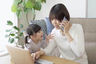 ノートパソコンで仕事をしてる主婦と子供