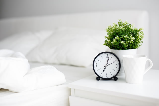 alarm clock and cup of coffee on bedside table and unmade bed at home or hotel