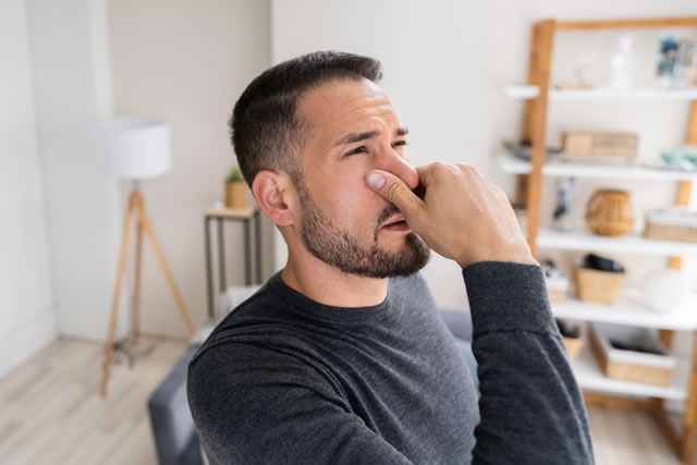 鼻をつまんでいる男性