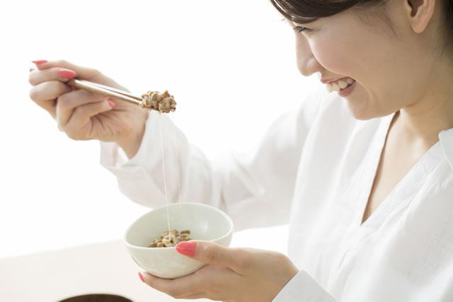 納豆を箸で掴む女性