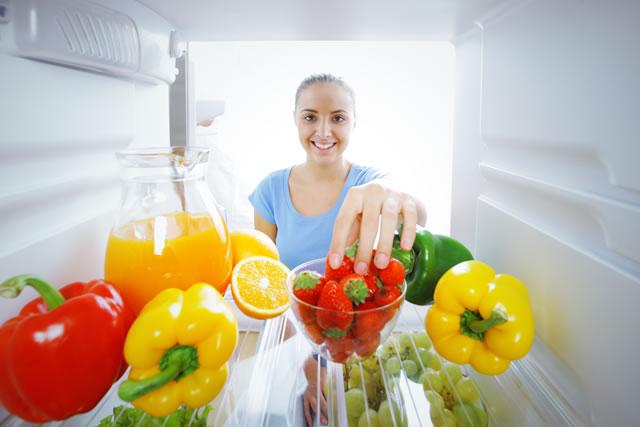 冷蔵庫の中身を取ろうとしている女性