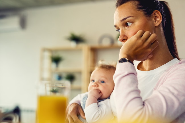 小さな子供を抱きながら感がごとをしている女性