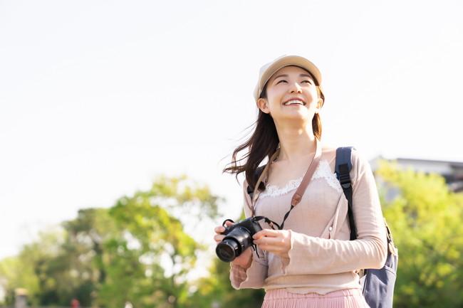 カメラを持って楽しそうに観光している女性