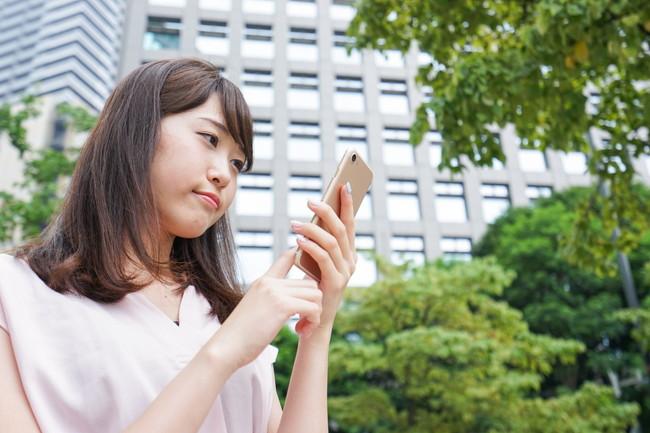 外でスマートフォンを操作している女性