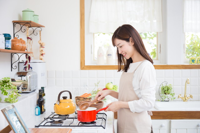 キッチンで赤い鍋を手にする女性