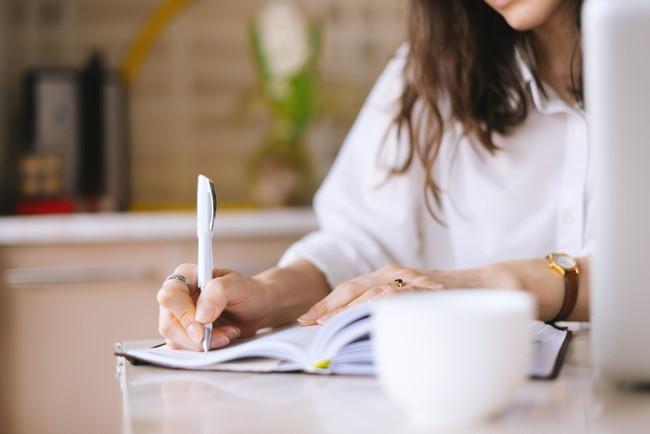 ノートに書き留めている女性