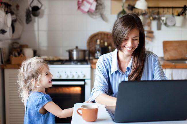 小さな女の子と笑顔でパソコンをしている女性