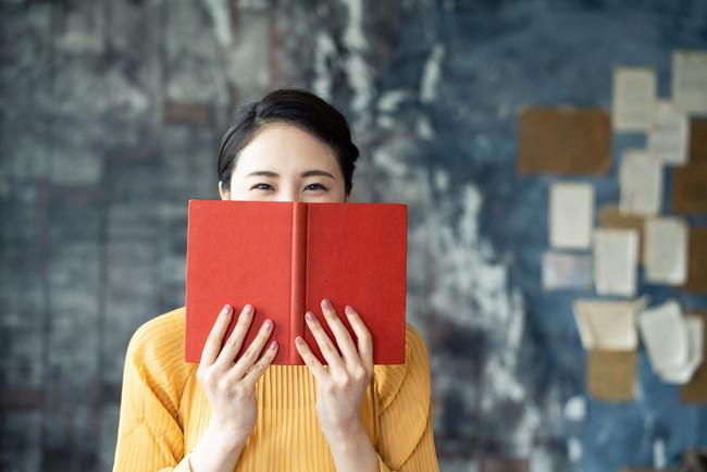 本をもって口元を隠している女性