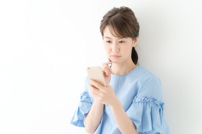 困った表情でスマートフォンを見ている女性