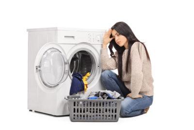 洗濯機が壊れて悩む女性