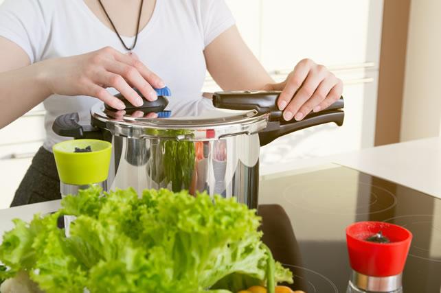 圧力鍋を開ける女性
