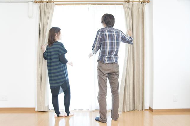 カーテンを開ける夫婦