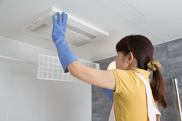 浴室の換気扇を掃除する女性