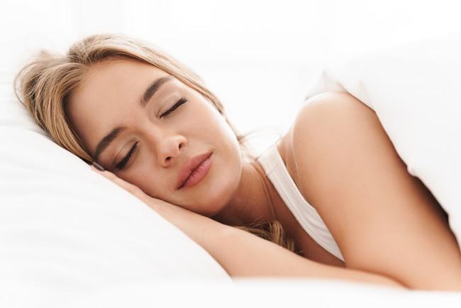 気持ちよさそうにベッドで横向きで眠っている女性