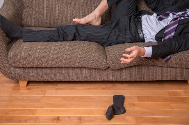 片方の靴下を脱いだままソファで寝てしまったスーツ姿の男性