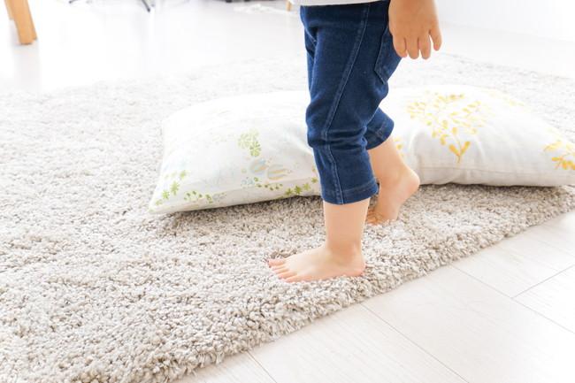 素足でカーペットの上で遊び子供