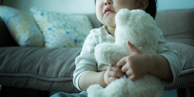 白いぬいぐるみを抱えている子供