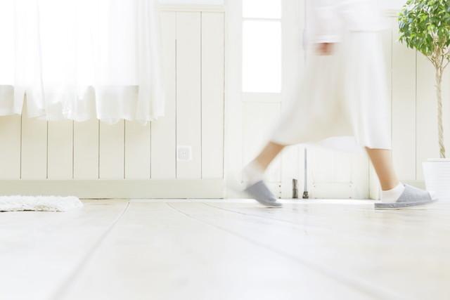 白いリビングを歩く女性の足元