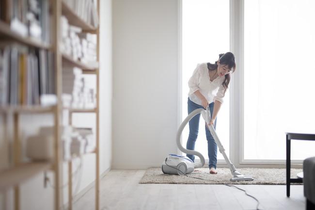 部屋を掃除機で掃除している女性