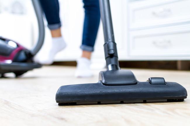 掃除機で床を掃除しているところ
