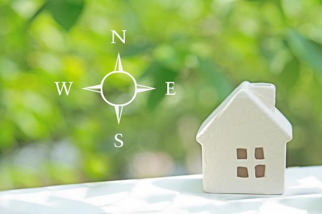 緑を背景にした方位図と白いミニチュアハウス