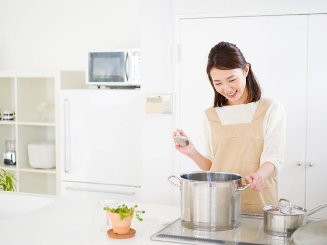 大きなシルバーの鍋で調理する女性