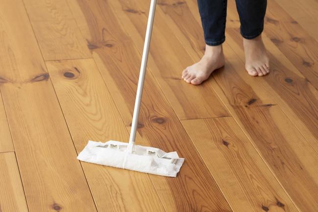 木目の床をモップがけする若い女性の足元