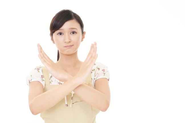 腕でバツ印を示すエプロン姿の女性