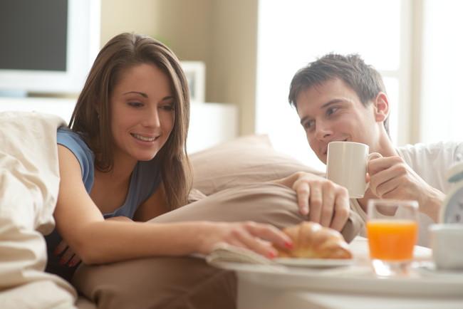 ベッドで朝食をとる夫婦