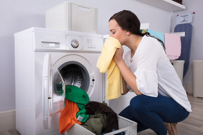 洗濯機から取り出したタオルの匂いを嗅ぐ女性