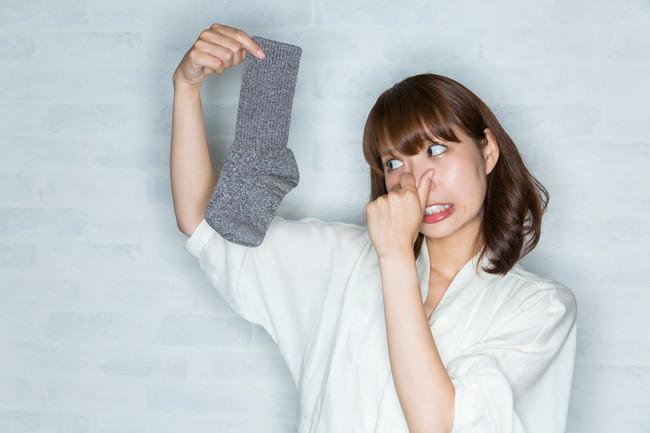 鼻をつまんで靴下をもつ女性
