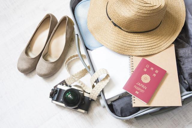旅行の準備、スーツケースにパスポートやカメラ