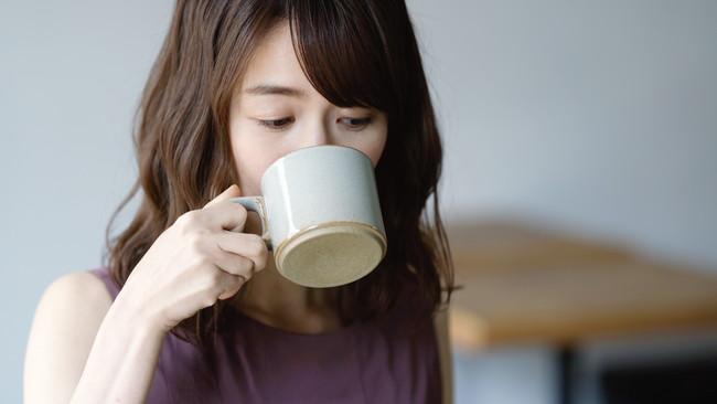 コーヒーカップでコーヒーを飲む女性