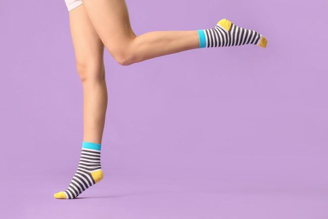 ボーダー柄の靴下をはいている女性の脚