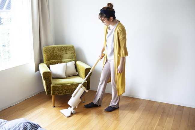 床に掃除機掛けをする女性