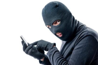 目だし帽をかぶってスマホを操作している犯罪者らしき男