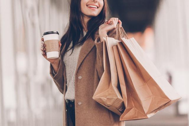 飲み物と紙袋を持った女性