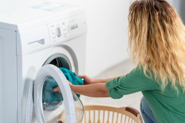 乾燥機から衣類を取り出す女性