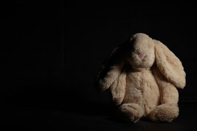 黒背景の中に置かれたウサギのぬいぐるみ