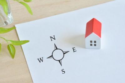 白い紙の上の方位図とミニチュアハウス