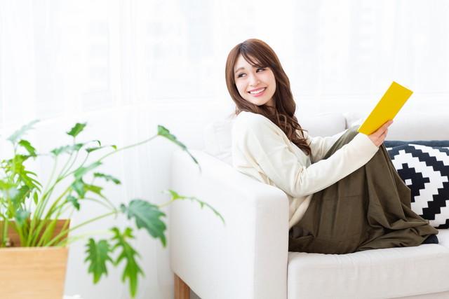 リビングのソファーで本を読む女性