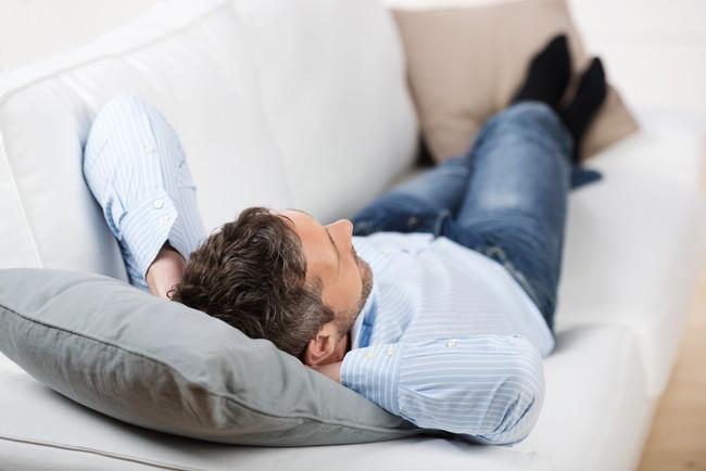 ソファで寝転んでいる男性
