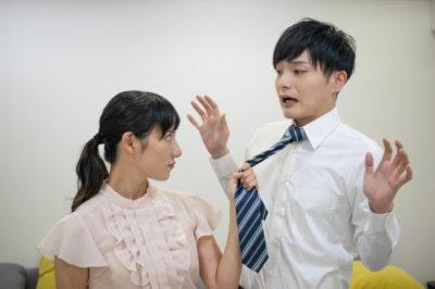 夫のネクタイをつかんで怒った顔をしている女性