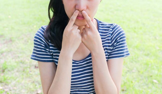 指を鼻に入れようとしている女性