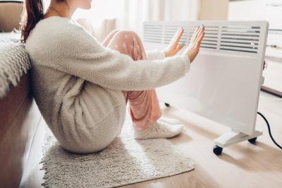 寝室のヒーターの前で暖まる女性