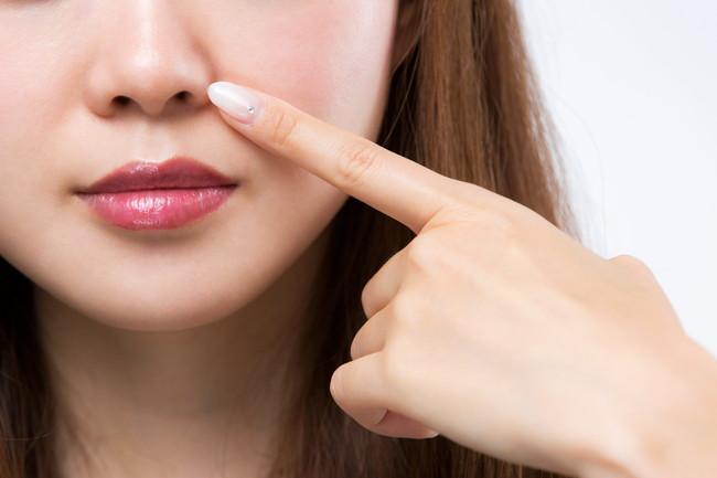 小鼻の指さしている肌のキレイな女性