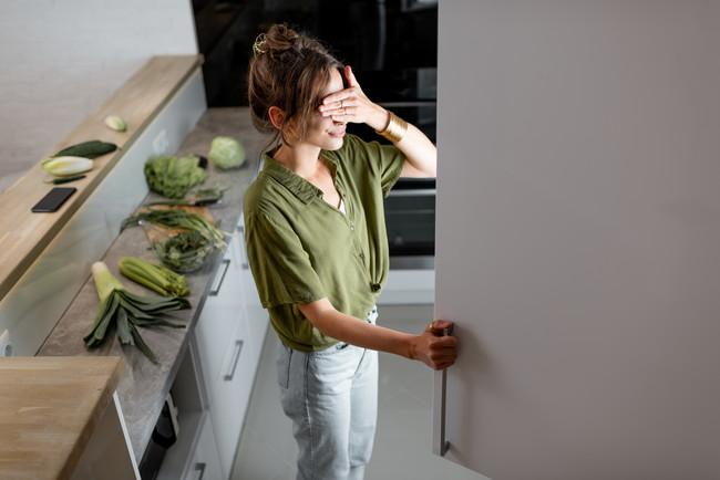 冷蔵庫を開けたものの中を見たくない様子の女性